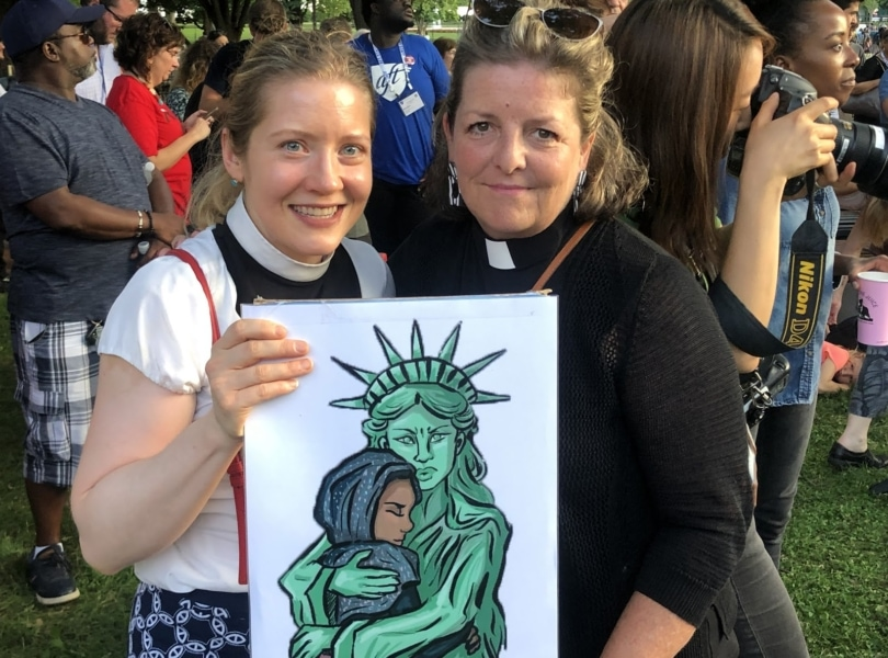 Two of Rock Spring's pastors hold a picture of the Statue of Liberty embracing an immigrant, while they demonstrate for immigration justice