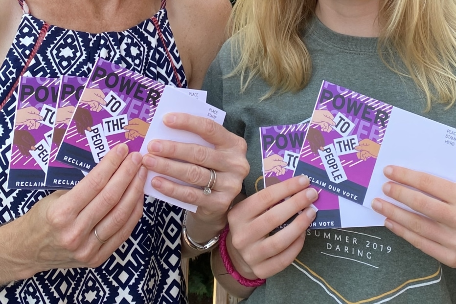 two women hold purple postcards for voting rights
