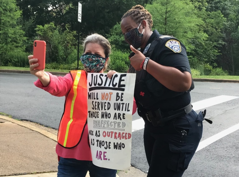 A woman holds a sign calling for racial justice and poses with a Black female police officer