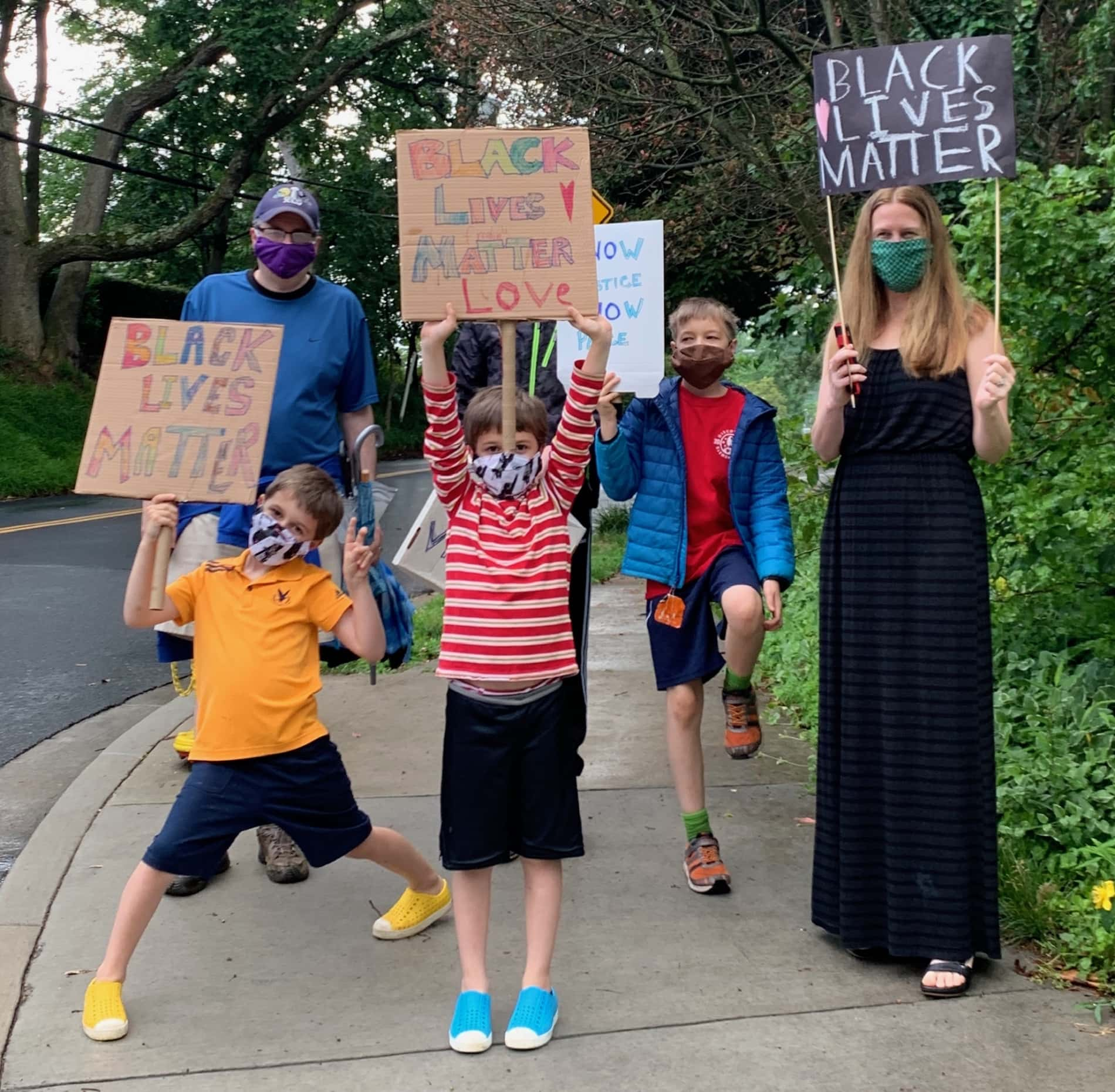 A family of five hold Black Lives Matter posters