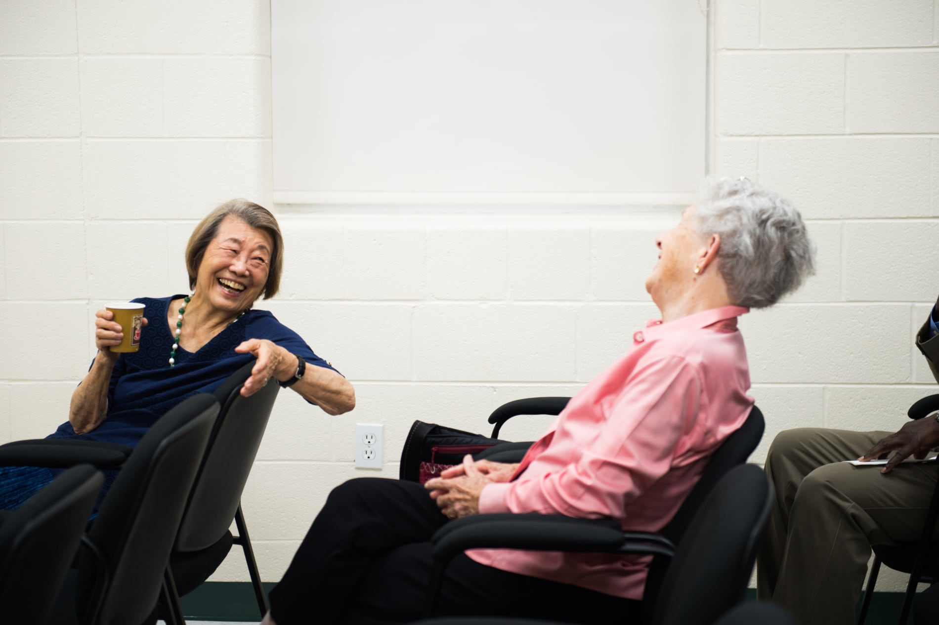 Two women laugh during a Bible study