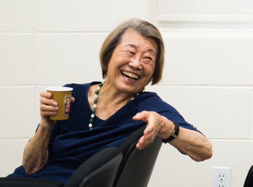 A woman laughs and gestures while holding a paper cup.