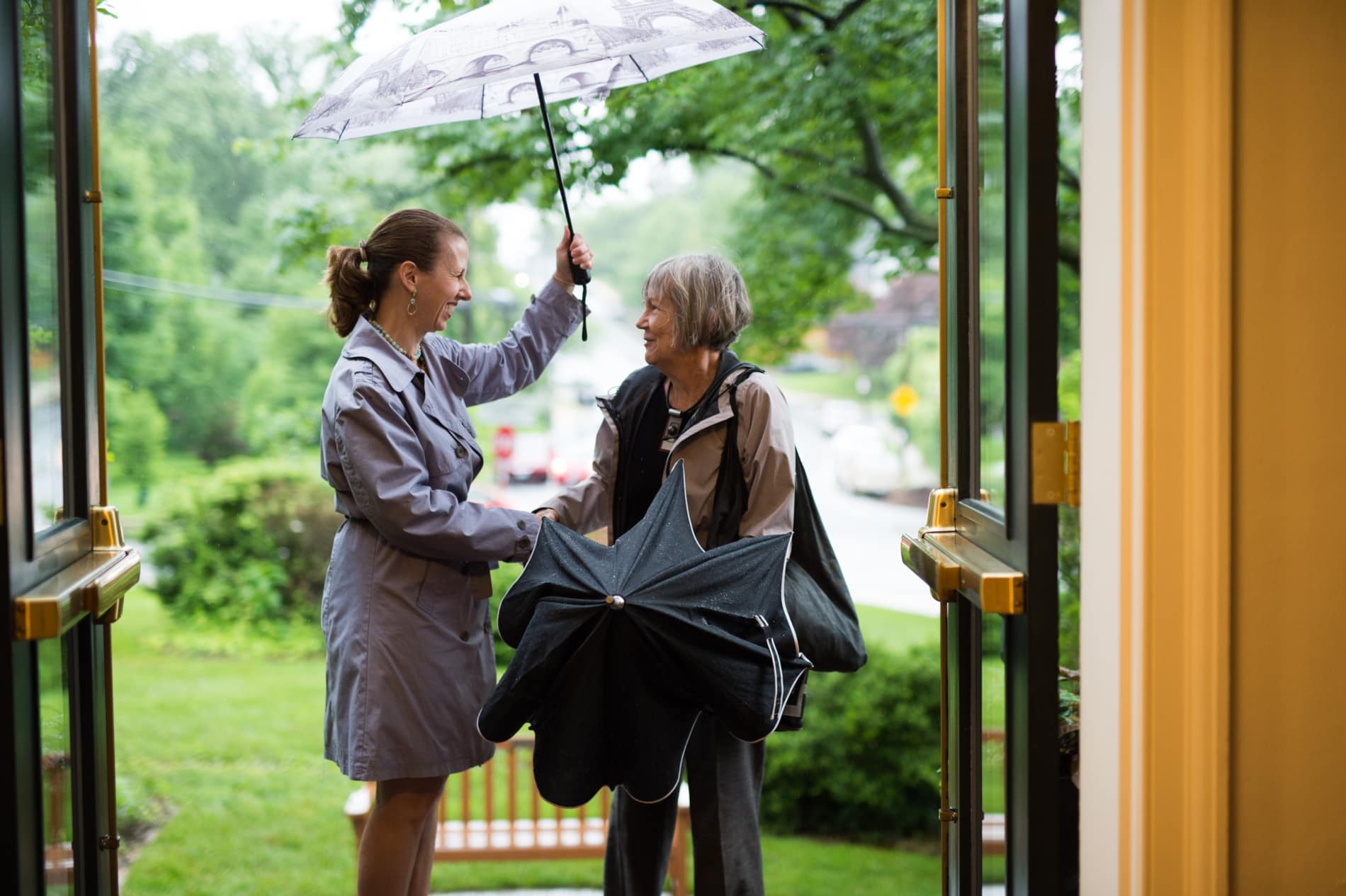 A woman holds an umbrella over another woman as she arrives at church