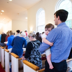 a man holds a toddler who is looking at the camera, surrounded by people standing in church pews