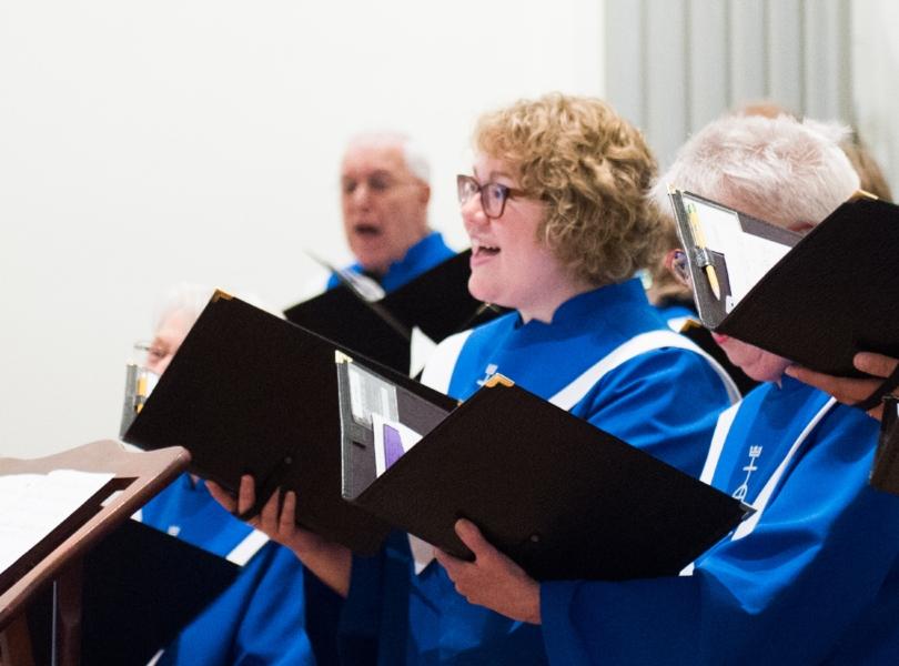 Choir members in blue robes holding music folders sing a hymn.