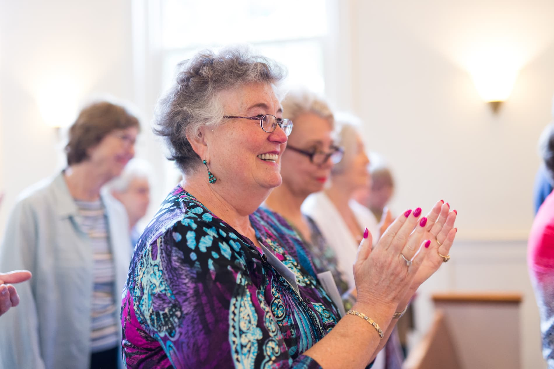 A woman claps during a hymn