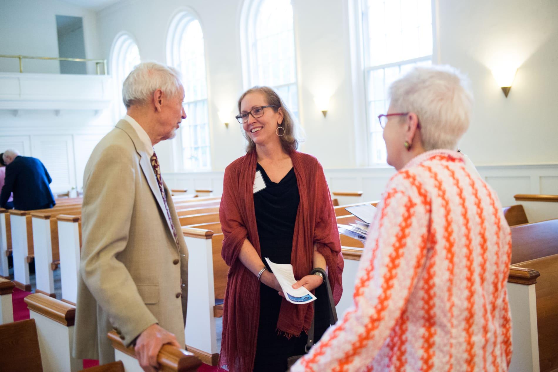Three adults talking in church