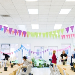 colorful flags decorate the ceiling of a large room set up with tables and chairs