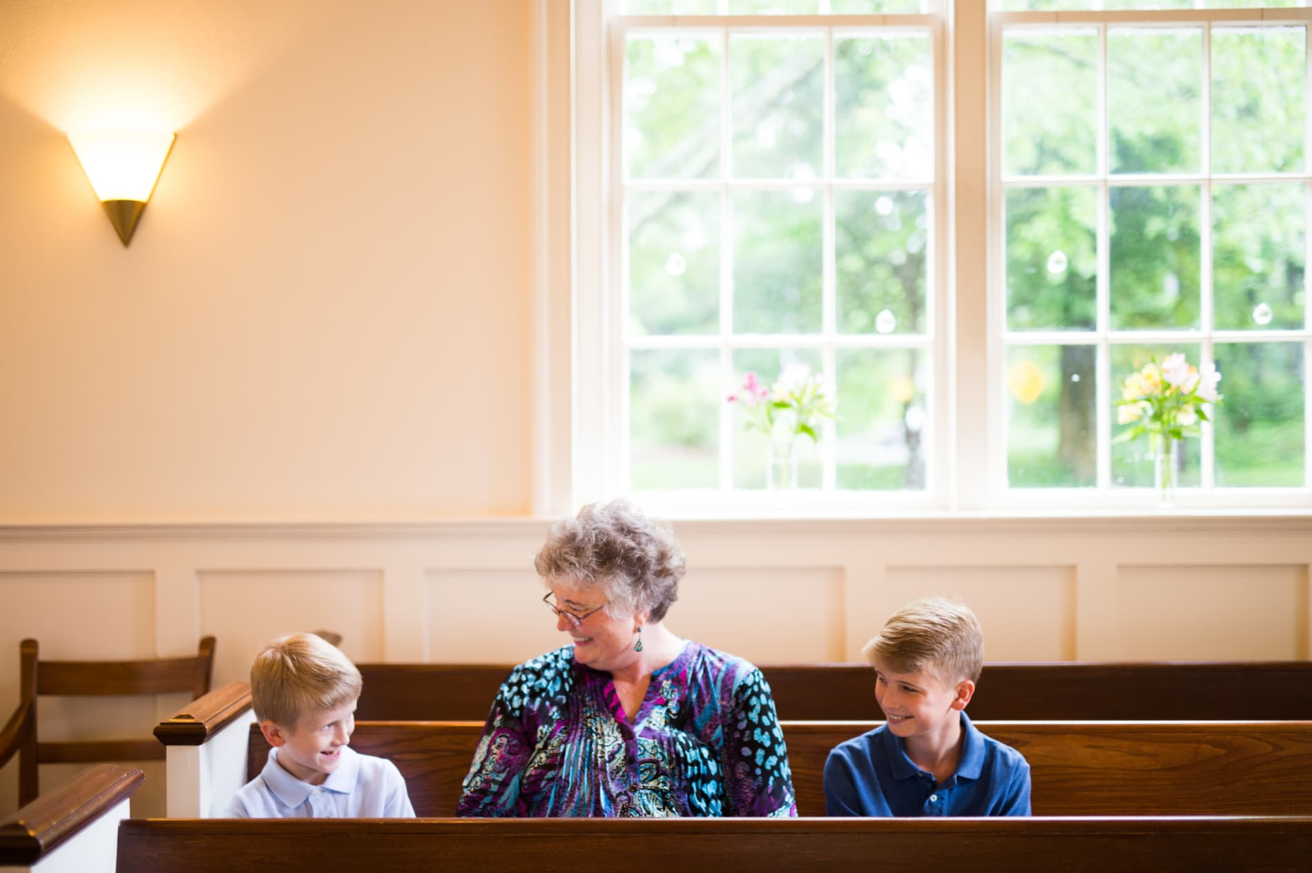 A grandmother and her two grandchildren sit in a pew