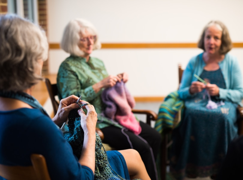 A group of three women knit and talk.