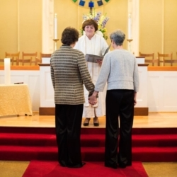 two women hold hands on the steps of a chancel in front of an officiant