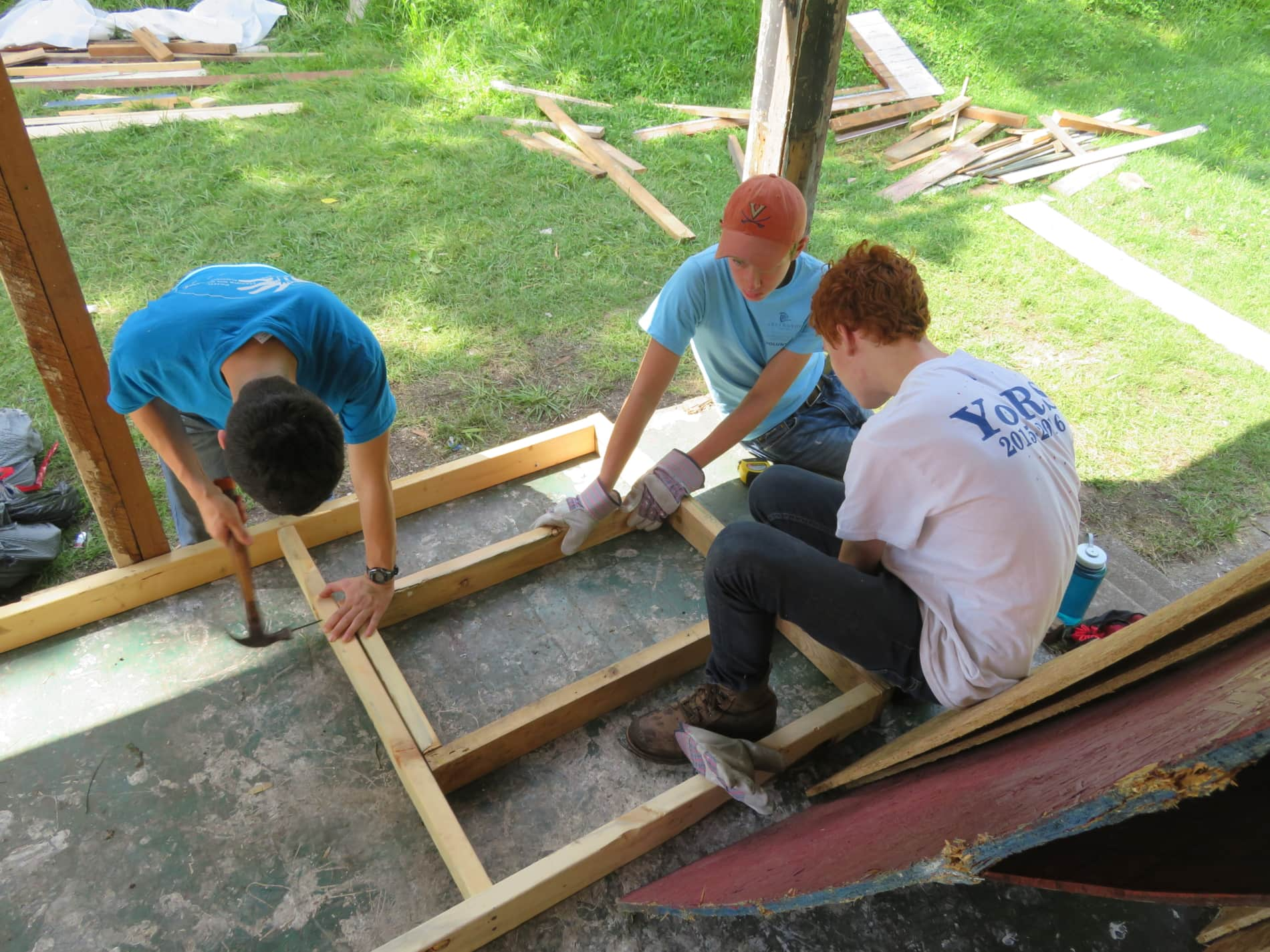 Three teenagers hammer pieces of wood together while on a youth service project.
