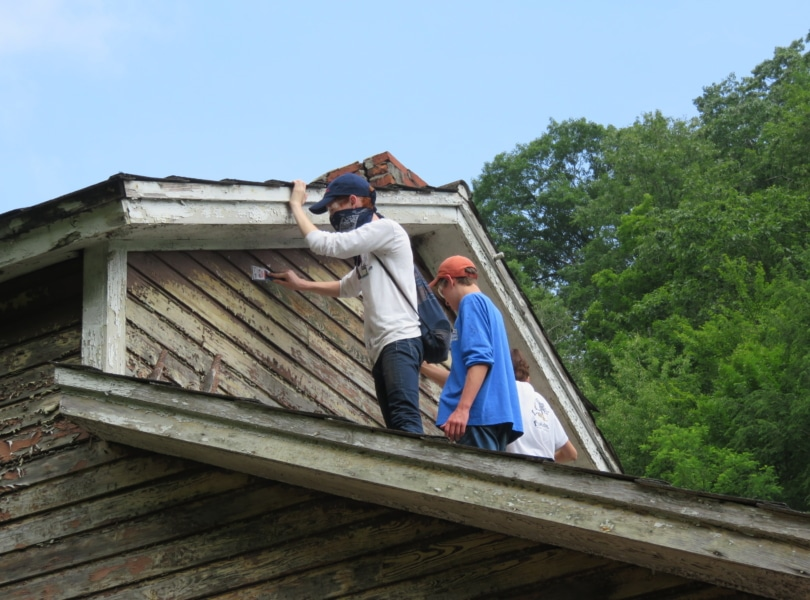 Two teenagers paint a house while volunteering on a youth service mission trip