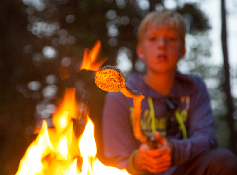 A child roasts a marshmallow over a campfire on a family retreat