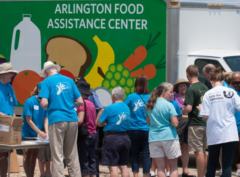 A group of people in blue tshirts stand in front of a green truck that says Arlington Food Asssitance Center during a volunteer event.