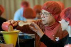 Volunteers in red hair nets measure grain for food kits for needy families.