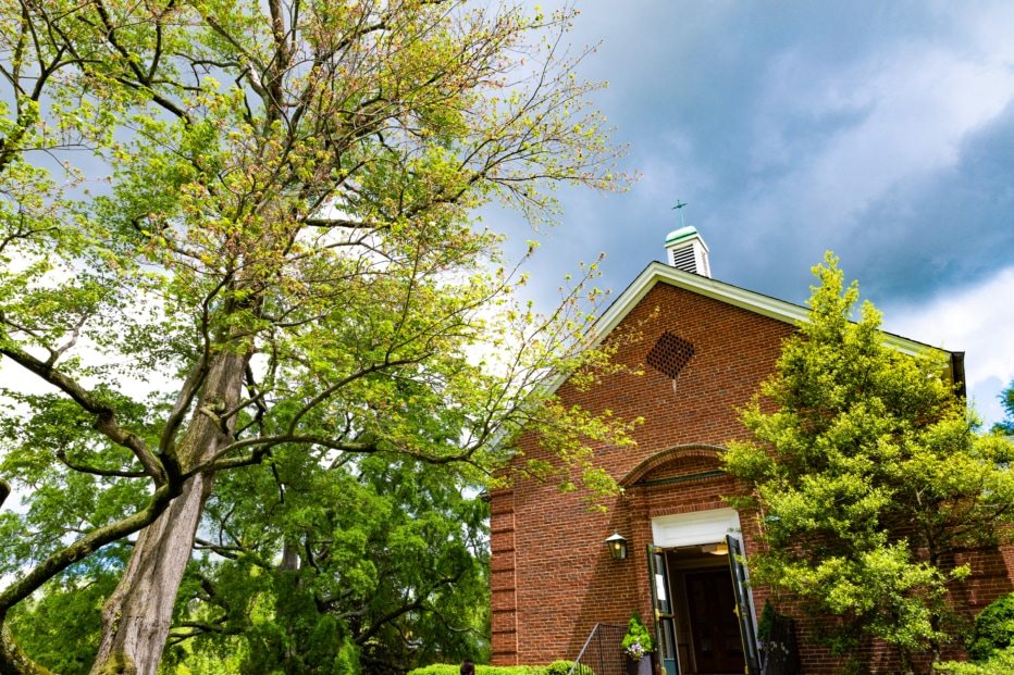 A large tree to the left of a brick church building with open doors.