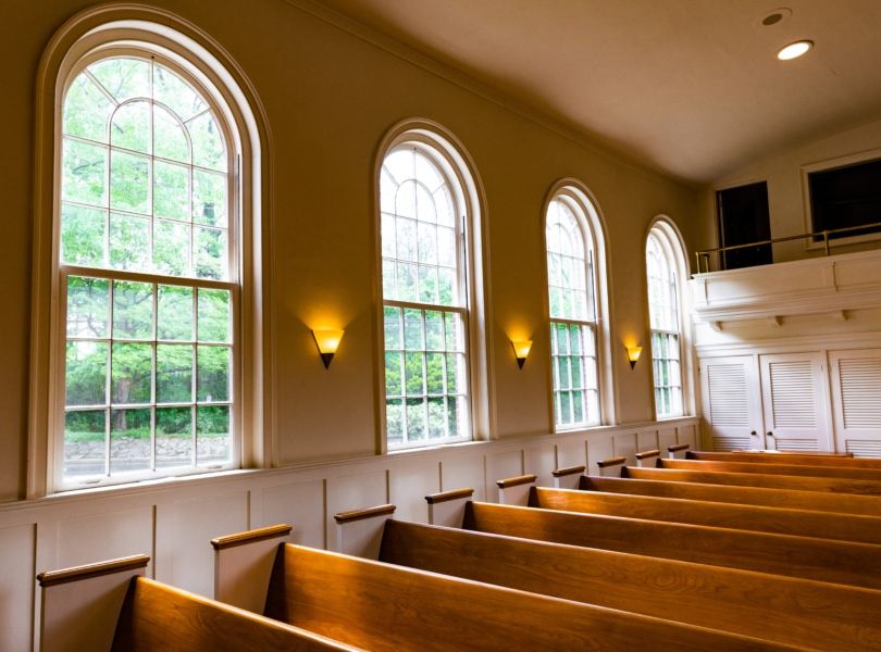 Large windows and wooden pews in the sanctuary of Rock Spring Church.