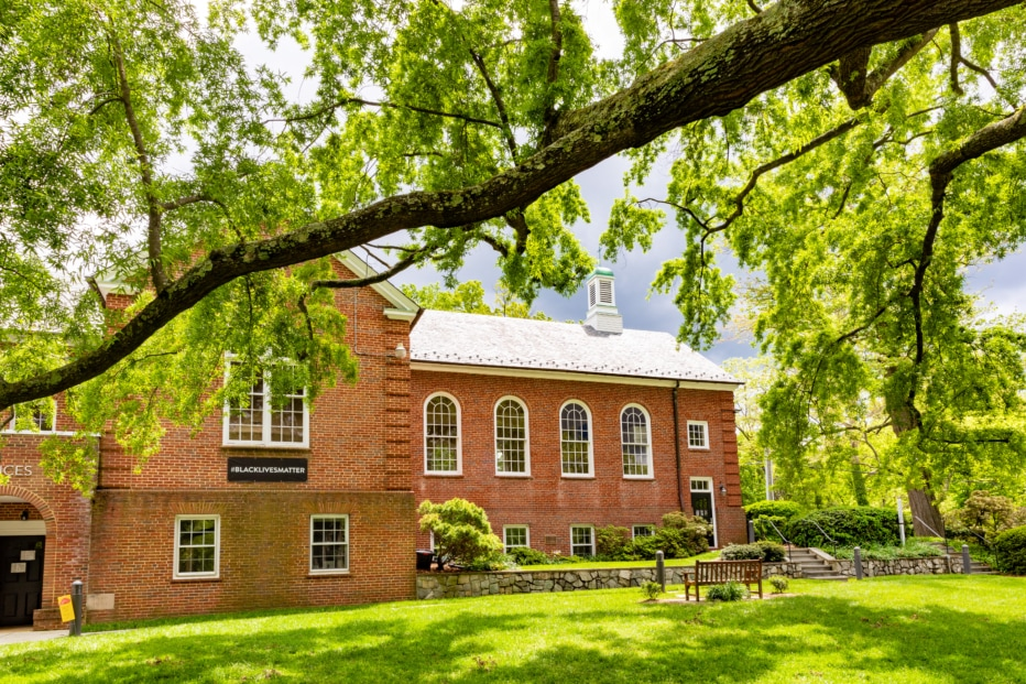 A brick building flanked by green lawn and trees.