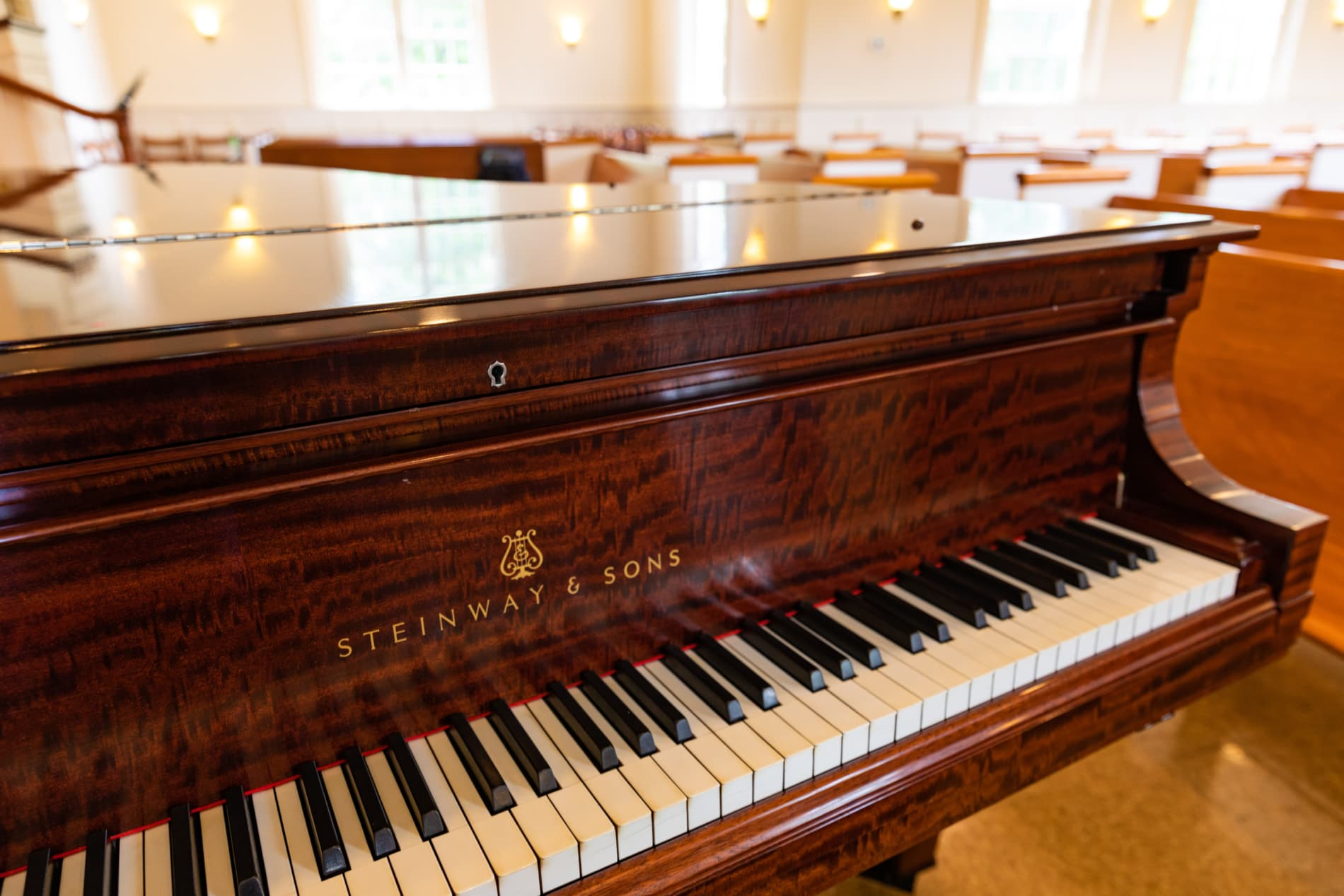 The keys and top of a Steinway piano against a background of church pews.