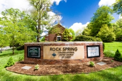 A large brick and stone sign that says Rock Spring Congregational United Church of Christ with lawn in front, and trees and a brick building in back.