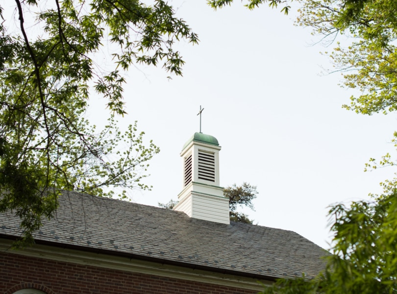 A brick church with a cross on its cupola