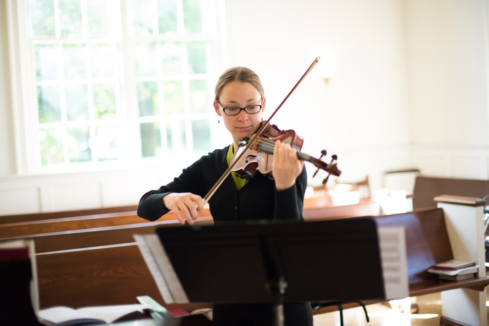 A young woman playing the violin stands in front of church pews and a bright window.