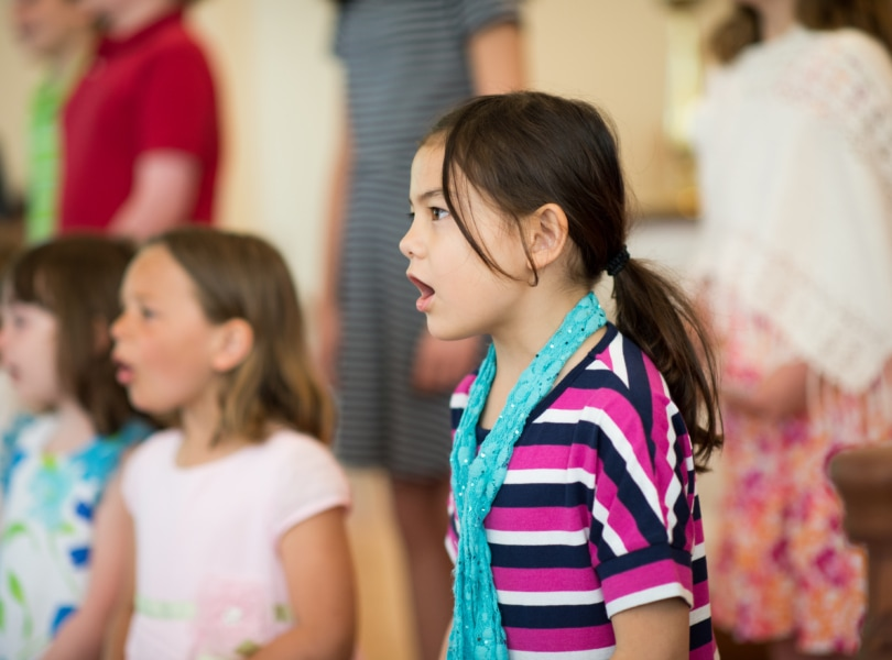 A young girl in a striped shirt stands and sings as part of a children's choir.