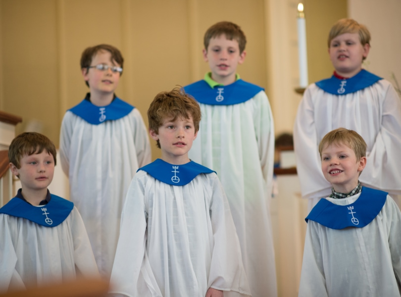 A group of boys in white choir robes sing in a church sanctuary.