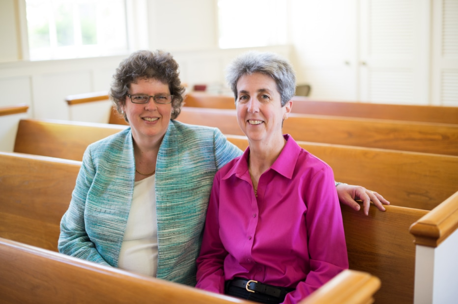 A woman sits with her arm around the woman next to her in the church pew.