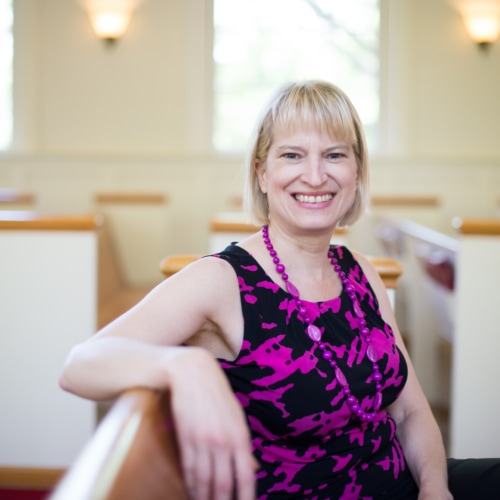 A smiling person in a pink and black dress sitting in a pew