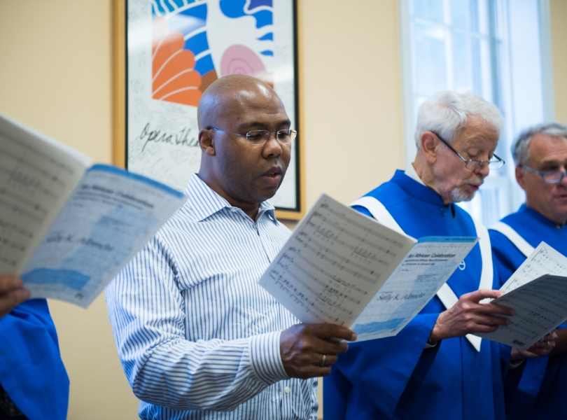 A group of men stand and sing holding sheets of music.