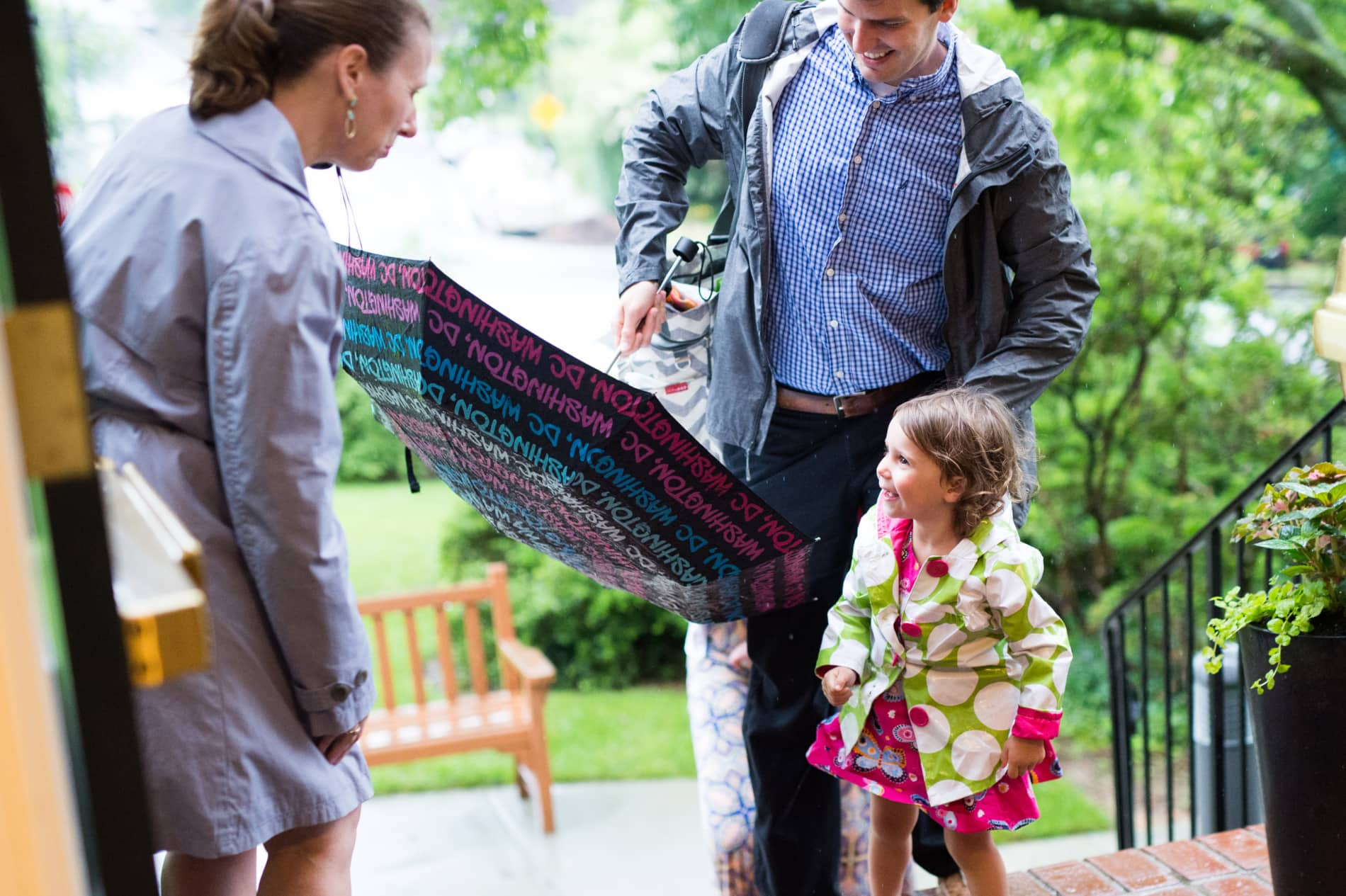 A woman bends down to talk to a young girl in a raincoat and her father holding an umbrella coming up brick steps.