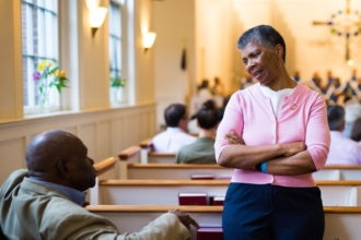 A seated man and a standing woman talk in the sanctuary of Rock Spring Church.