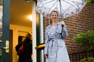 A woman in a coat holding an umbrella stands in front of open doors.