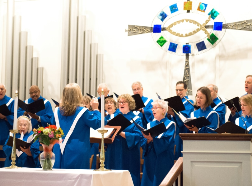 An adult choir in blue robes sings on risers with an altar table in the foreground and large decorative cross in the background.