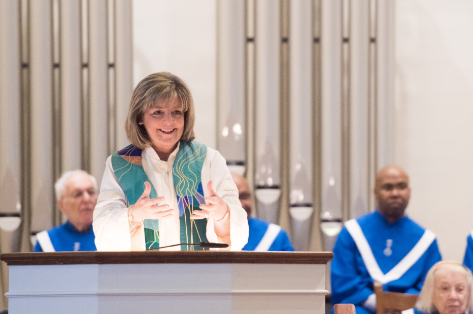 Rev. Kathy Dwyer stands and gestures at the pulpit with organ pipes and choir members in blue robes in the background.