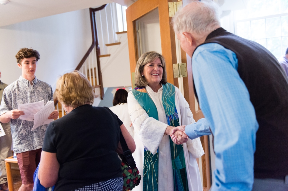 Rev. Kathy Dwyer shakes the hand of a man at the door to the Rock Spring sanctuary.