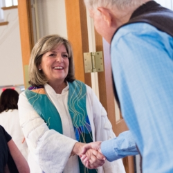 Rev. Kathy Dwyer shakes the hand of a visitor to church.