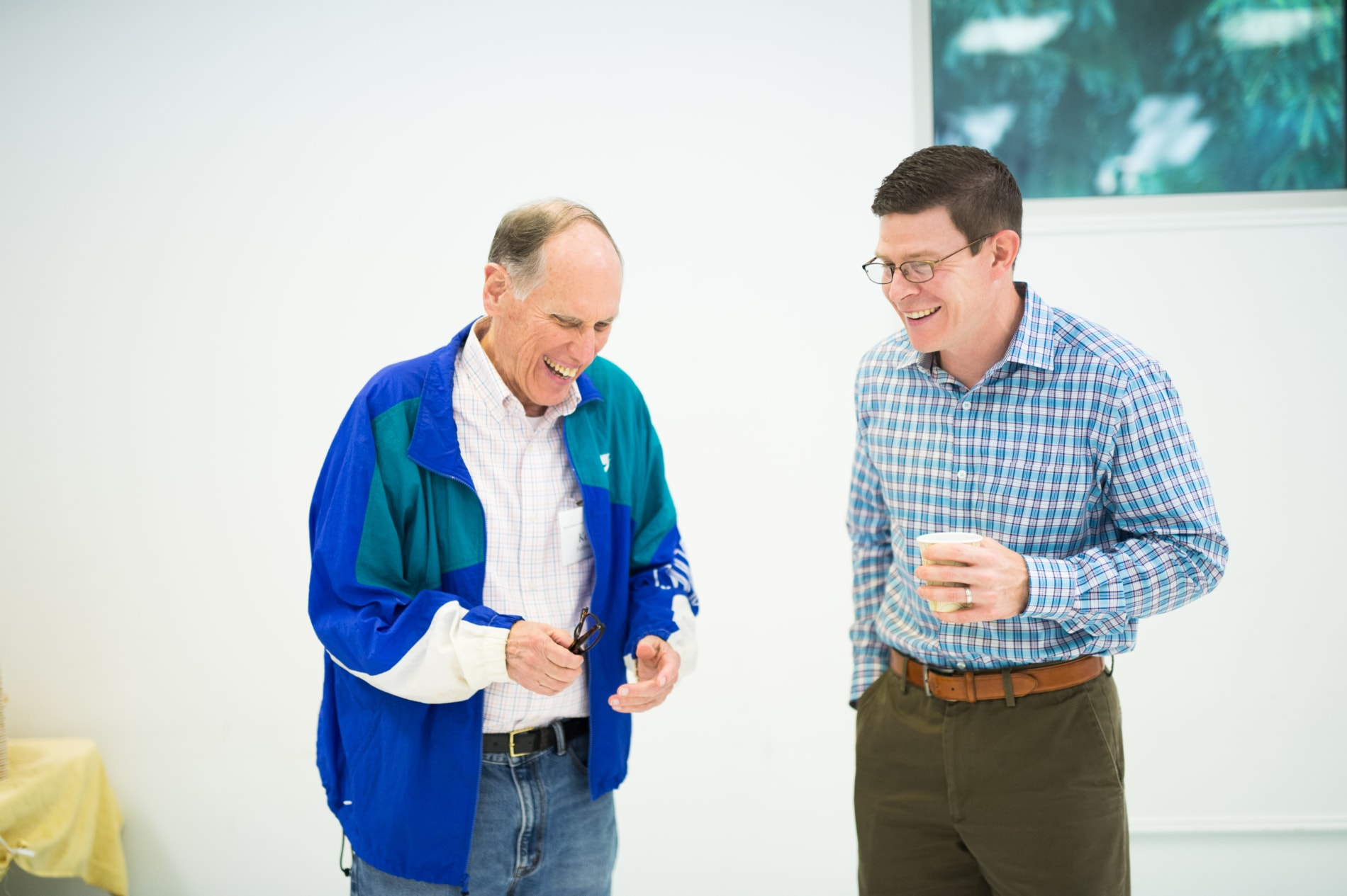 An older man and a younger man stand inside drinking coffee and laughing.