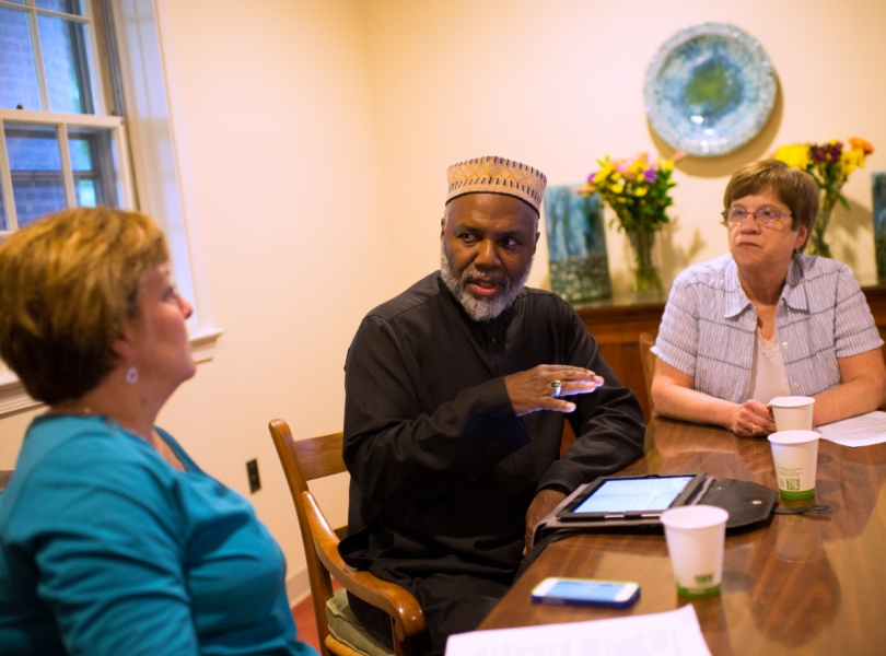 Red. Kathy Dwyer and a congregant engage in deep conversation with a Black clergyman
