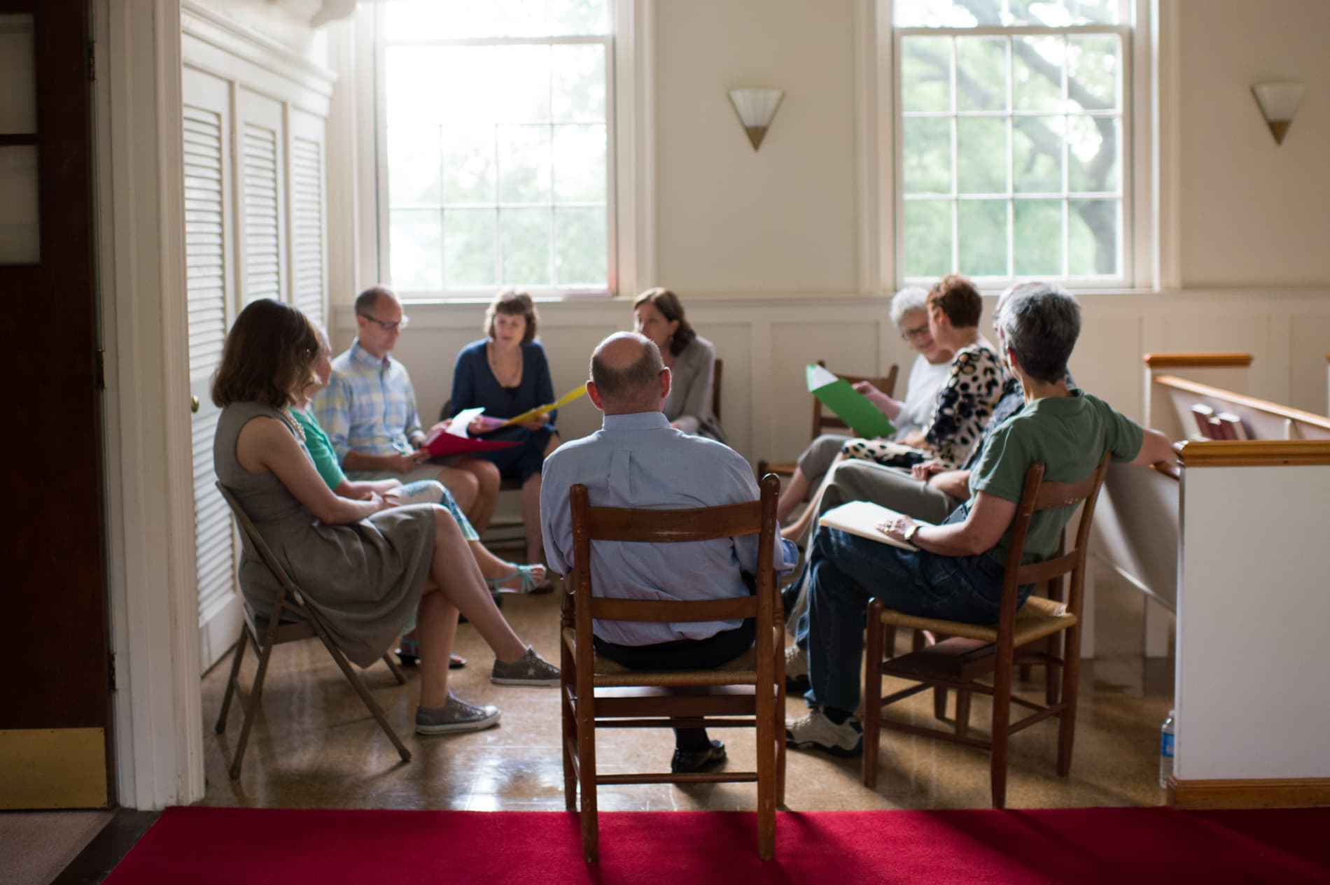 A group of adults sit in a circle in a Bible study class
