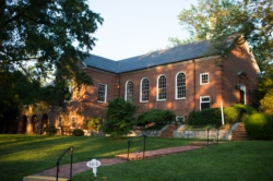 A brick walkway leading up to a brick church building with lawn and trees on either side.