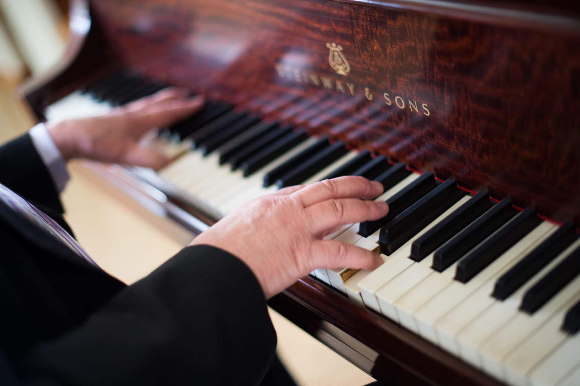 A close up of a man's hands playing a Steinway piano.