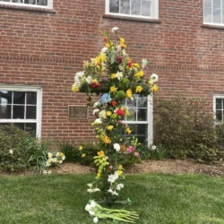 Spring flowers adorn a large cross set on a memorial terrace green.