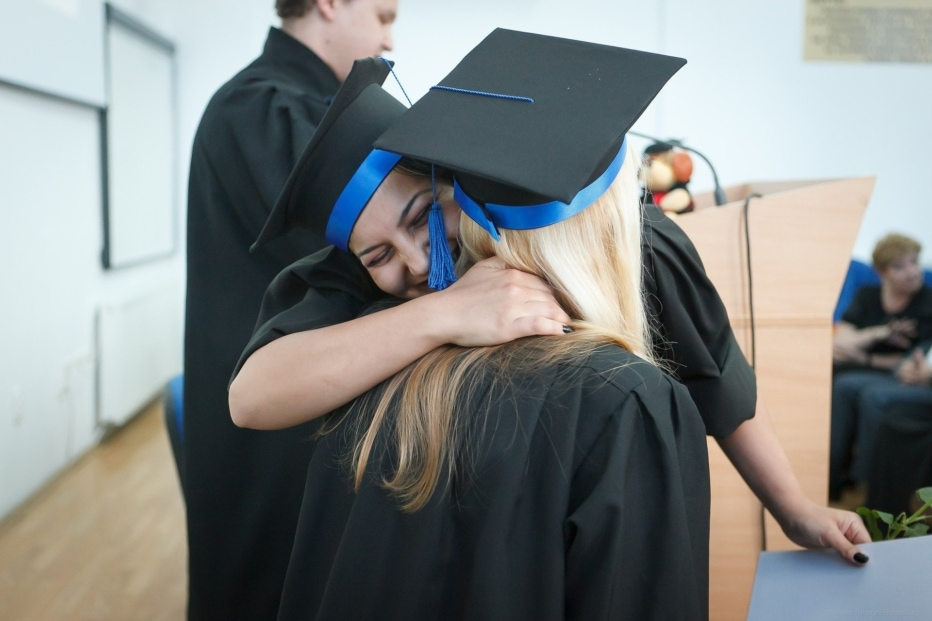 Two women in black graduation gowns and hats with blue ribbons hug at a graduation ceremony.