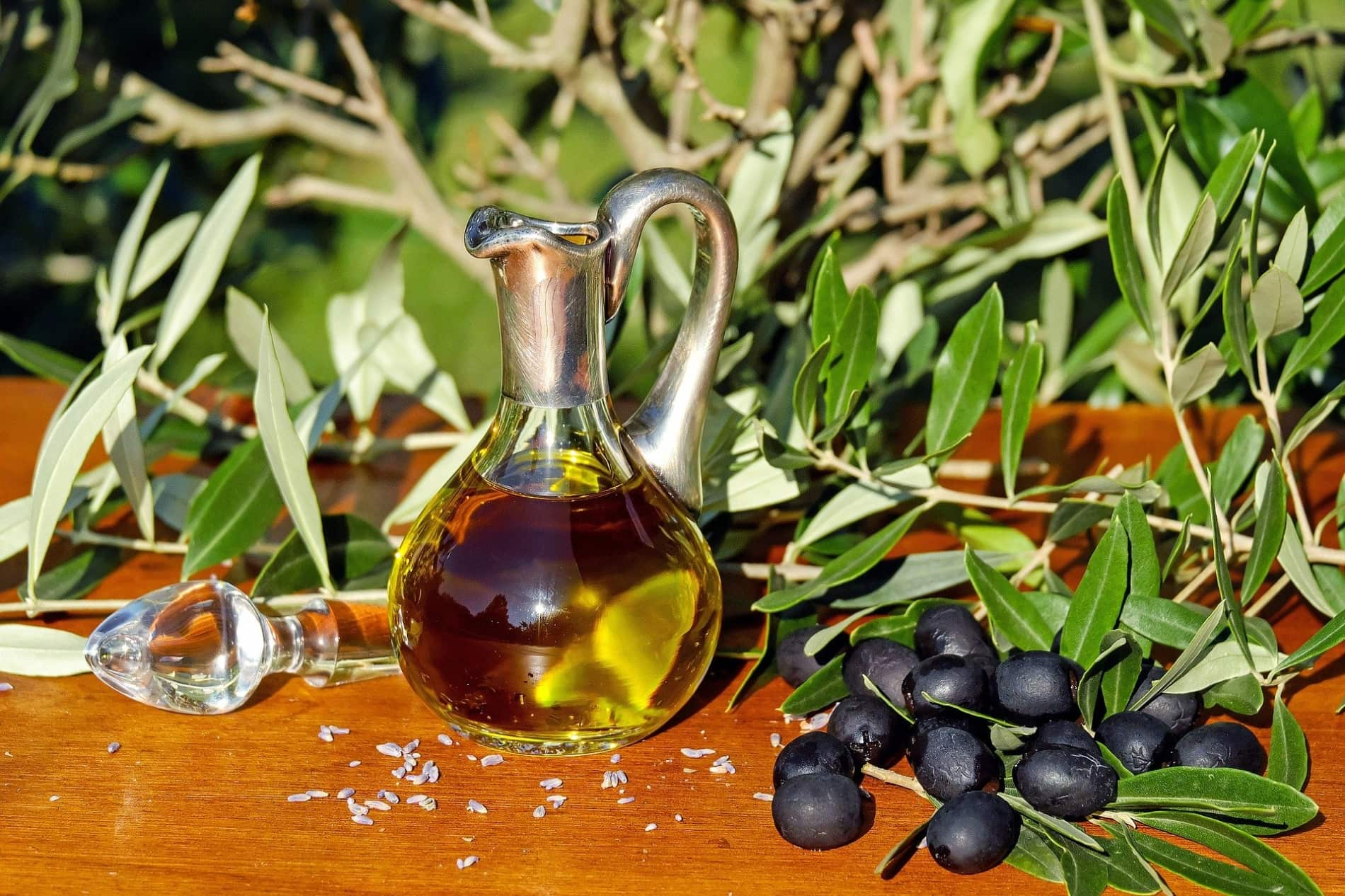 A small glass pitcher of olive oil next to fresh olives and olive branches.