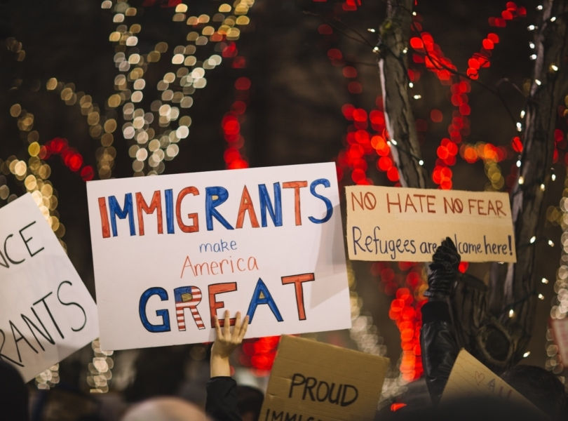 A group of demonstrators hold hand written posters in support of immigration justice with Christmas lights on trees in the background.