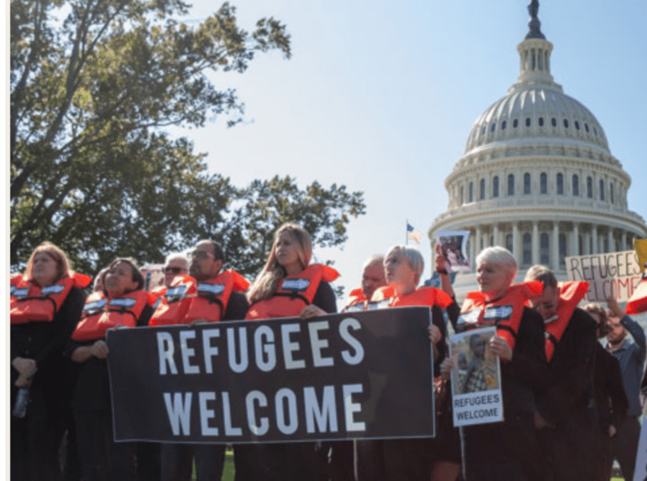 people wearing red life vests hold a banner that says