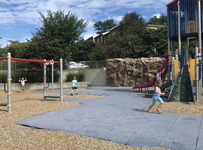 a playground on a sunny day with children running